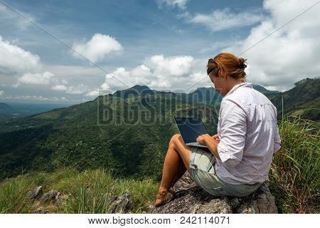 Caucasian Girl Working On Her Computer On The Top Of The Mountain. Concept Or Remote Work In Interne