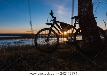 Silhouette Of A Bicycle Standing Near A Tree On The River Bank Against The Backdrop Of The Setting S