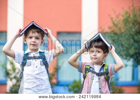 Two Children Of Younger School Age, The Boy And His Friend Are Reading Books On The Green Grass.