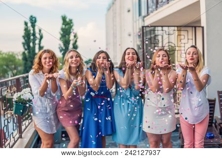 Girls Party. Beautiful Women Friends On The Balcony Having Fun At Bachelorette Party. They Are Blowi