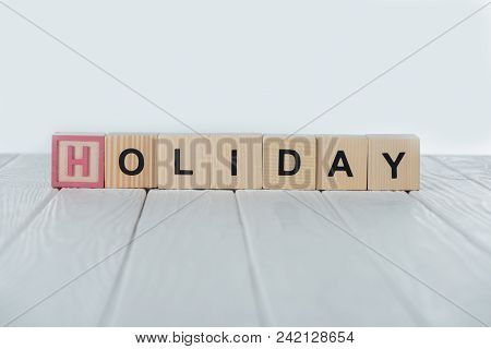 Close Up View Of Holiday Word Made Of Wooden Cubes On White Wooden Tabletop