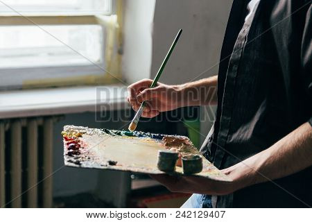 Across From The Window The Artist Holds A Palette With Paints And A Brush And Is Going To Paint On C