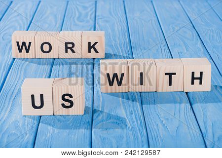 Close Up View Of Arranged Wooden Blocks Into Work With Us Phrase On Blue Wooden Surface
