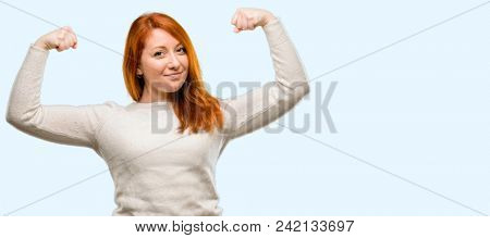 Beautiful young redhead woman showing biceps expressing strength and gym concept, healthy life its good isolated over blue background