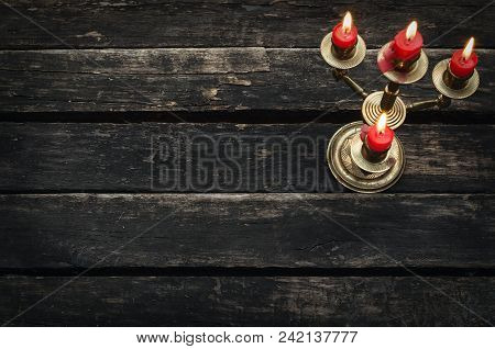 Old Candlestick With Four Burning Candles On An Empty Wooden Table Background With Copy Space.