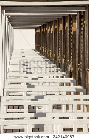 Perspective View Of The White Beach Huts. Infinite Background. The Cabins On The Beach In Succession
