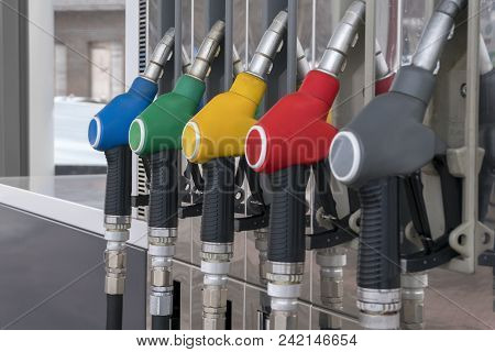 Blue, green, yellow, red and gray fuel pistols on fuel station close-up