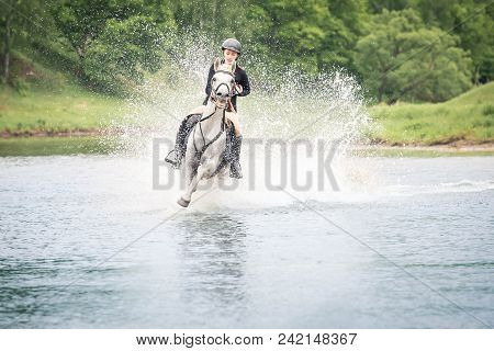 May 20, 2018. Moscow. One Horsewomen Force By Wading The River Astride Horses. On A Background Green