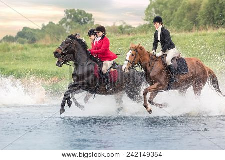 May 20, 2018. Moscow. Three Horsewomen Force By Wading The River Astride Horses. On A Background Woo