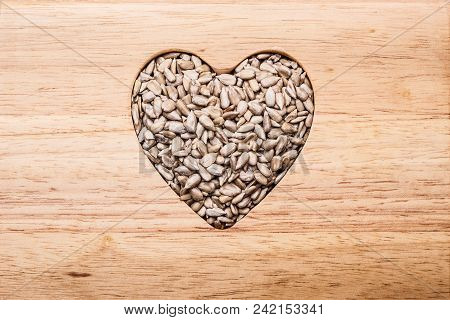 Whole Food. Heart Shaped Sunflower Seeds On Wood Surface Background