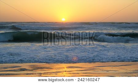 A Beautiful Sunset Beach In California With The Sun Reflecting Off The Sand.
