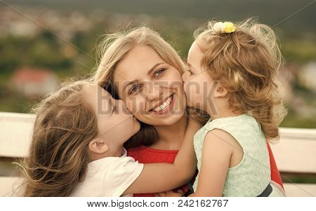 Childhood. Happy Woman. Happy Childhood, Family, Love. Daughters Kiss Mother On Natural Landscape. M
