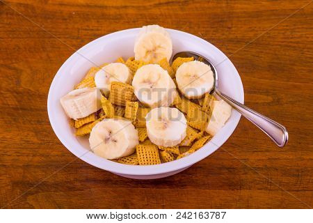 A Crunchy, Square, Corn Cereal With Sliced Bananas In A White Bowl On A Wood Table