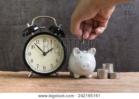 Long Term Financial Saving And Investment Account, Hand Putting Coin Into Piggy Bank With Stack Of C