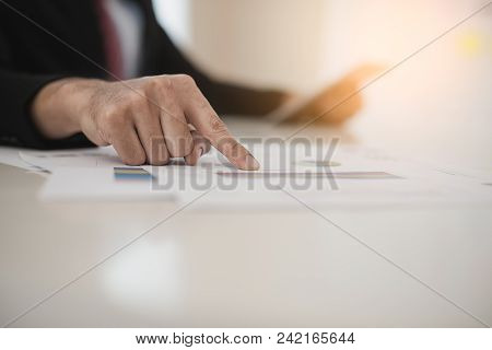 Hand Of Businessman Working On Data Charts And Digital Tablet At Office Desk. Analyzing Brainstormin