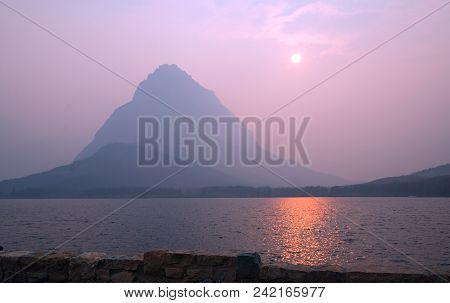View From Many Glacier Hotel Of Smoky Sunset Over Swiftcurrent Lake In Front Of Grinnell Point In Th