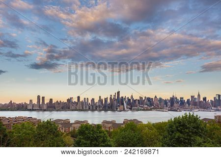 New York City midtown Manhattan sunset skyline panorama view from Boulevard East Old Glory Park over Hudson River. poster