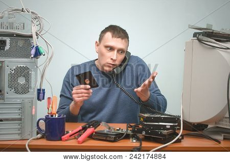Computer Technician Engineer Is Holding In One Hand A Floppy Disk Drive And Speaking On The Phone By