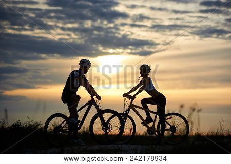 A Man And A Woman On Bicycles Stand On The Road Among The Field Grass Opposite Each Other And Look T