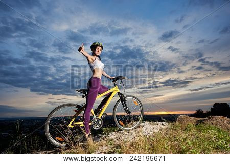 View Of Positive And Beautiful Girl In Violet Leggings, White Top And Helmet Smiling And Posing With