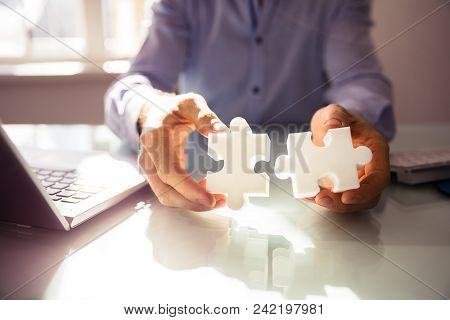 Businessperson's Hand Holding Two Jigsaw Puzzle