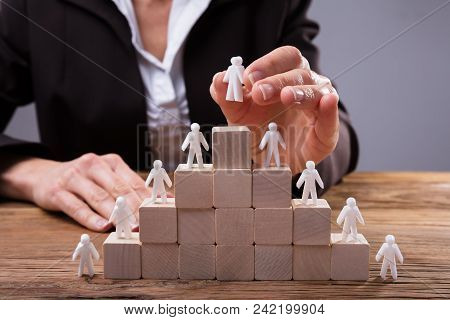Close-up Of A Businessperson Placing Human Figures