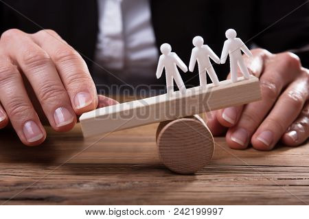 Businessperson Placing Finger On Seesaw Against White Human Finger