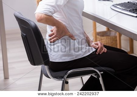 Close-up Of A Businessperson Sitting On Chair Suffering From Back Pain