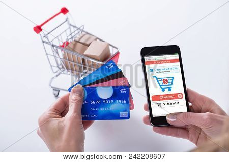 Close-up Of A Person Shopping Online With Credit Cards On Mobile Phone Against White Background