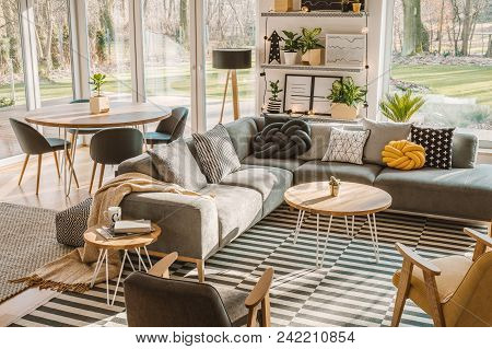 High Angle View Of A Stylish, Nordic Living Room Interior With A Wooden Dining Table, Gray Sofa And
