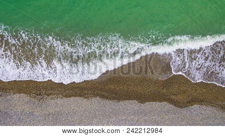 Top-down Drone View Of The Seacoast With The Surf And The Pebble Beach