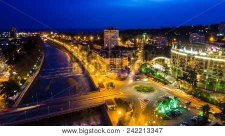 Drone View Of Kubanskiy Bridge Over Sochi River, Buildings And Streets Of The City Of Sochi At Dusk,