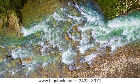 Top-down Drone View Of Rapids Of Mountain River With Wet Boulders And Pebble Shore