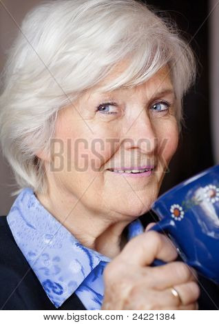 Senior woman drinking coffee and smiling