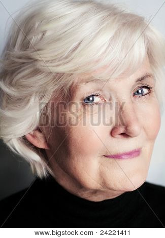 Senior lady portrait with black pullover on grey background, looking sceptically with humour