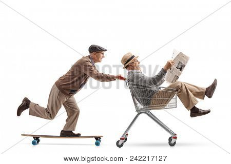 Senior riding a longboard and pushing a shopping cart with another senior riding inside it and holding a newspaper isolated on white background