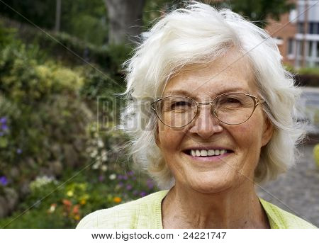Senior woman portrait, outdoor in front of house and garden