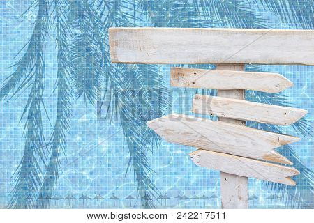 White rustic wood arrow signs over turquoise blue mosaic pool water with palm leaves and parasols surface summer theme travel vacation background. poster