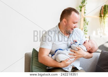 Image of young father with newborn son sitting on sofa