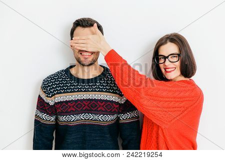 Indoor Shot Of Attractive Brunette Female With Positive Expression, Covers Man`s Eyes, Wear Winter S