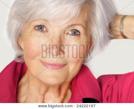 Senior Woman Portrait mit weißem Haar und rote Bluse, Links halten arm auf der Seite und hat die han