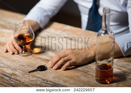 alcohol abuse, drunk driving and people concept - close up of male driver hands with brandy glass and car key on table at night