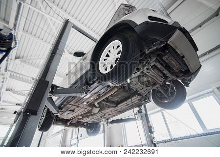 Car On A Wheel Alignment Lift In Auto Service. Diagnosis Of The Chassis Of The Car Raised At The Ele