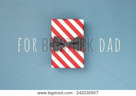 One Gift Box Wrapped In Red Striped Paper And Tied With The Grey Bow Tie On Blue-gray Background. Th