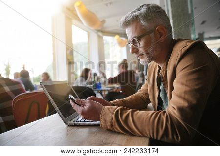 Middle-aged man in trendy restaurant using smartphone