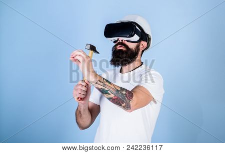 Builder And Renovation Concept. Man With Beard In Vr Glasses Holds Hammer, Light Blue Background. Gu