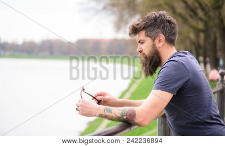 Man With Beard And Mustache With Sunglasses, Riverside On Background. Hipster On Thoughtful Face Sta