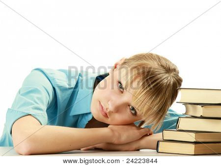 Portrait of beautiful tired blonde student girl sitting among  books. Isolated on white background