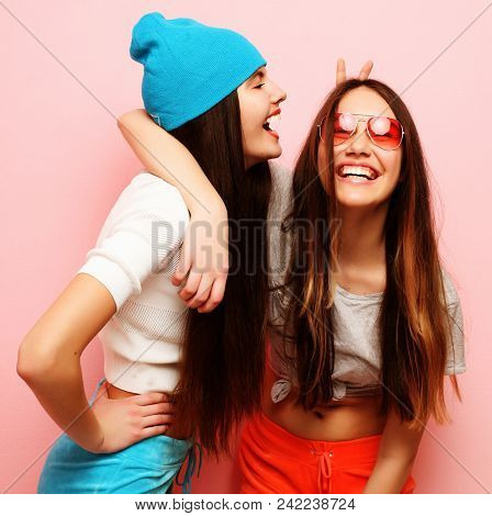 lifestyle, people and friendship concept - happy smiling pretty teenage girls or friends hugging over pink background