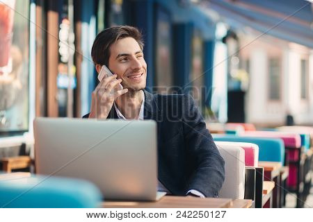 Multitasking. Young Businessman Working On Laptop And Talking On Phone, At The Table On Colorful Caf